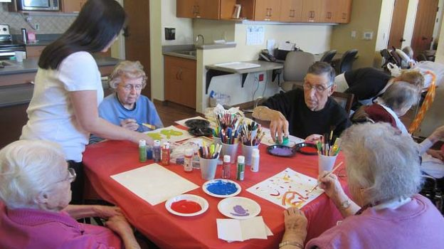 """Sophia Helping Seniors Paint"" by Ann licensed under CC BY 2.0"