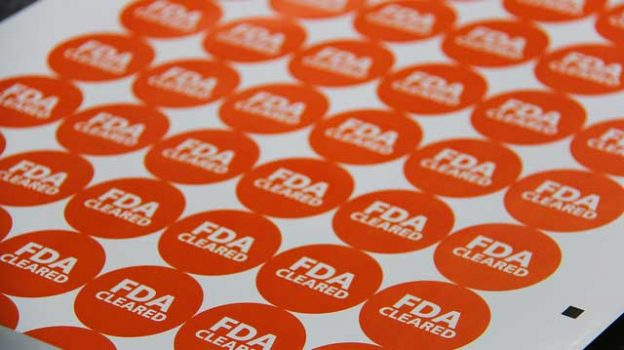 """FDA Cleared"" by StickerGiant Custom Stickers licensed under CC BY 2.0"