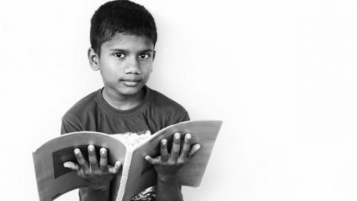 """""""Indian School Boy Reading the Book"""" by Nithi Anand licensed under CC BY 2.0"""