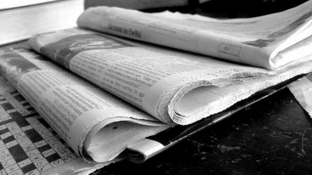 """Newspapers B&W"" by Jon S licensed under CC BY 2.0"