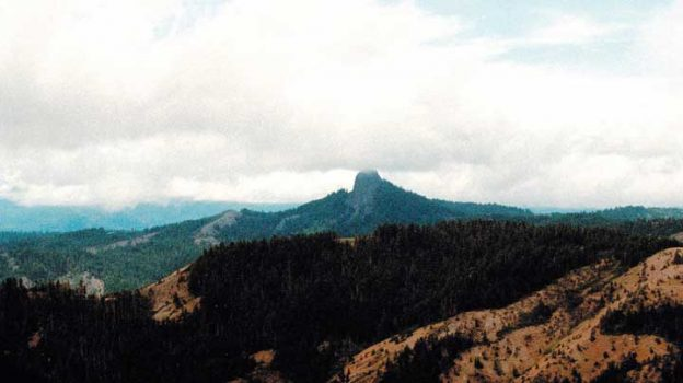 """FILE- In this July 6, 2000, file photo, Pilot Rock rises into the clouds in the Cascade-Siskiyou National Monument near Lincoln, Ore. After touring the """"unique"""" Cascade-Siskiyou National Monument in Oregon and speaking to ranchers, loggers and environmentalists, U.S. Interior Secretary Ryan Zinke must next make a recommendation on whether it should be abolished or resized. (AP Photo/Jeff Barnard, File)"""