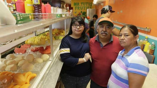 In this June 27, 2017 photo, from left, Diana Resendiz, Alberto Resendiz, and Maribel Resendiz, pose for a photo at their business Mr. Tutis Fruties in Florida City, Fl. Maribel Resendiz and her husband came to the U.S. from Mexico, sold cool drinks to workers in the tomato fields of South Florida and eventually opened a bustling shop in a strip mall offering fruit smoothies and tacos. Now she is preparing for the possibility she'll have to leave it all behind. (AP Photo/Lynne Sladky)
