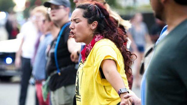 Alissa Ellis chants while blocking an intersection during a rally Monday, Aug. 14, 2017, in Durham, N.C. Protesters toppled a nearly century-old statue of a Confederate soldier Monday at the rally against racism. The Durham protest was in response to a white nationalist rally held in Charlottesville, Va., over the weekend. (Casey Toth/The Herald-Sun via AP)