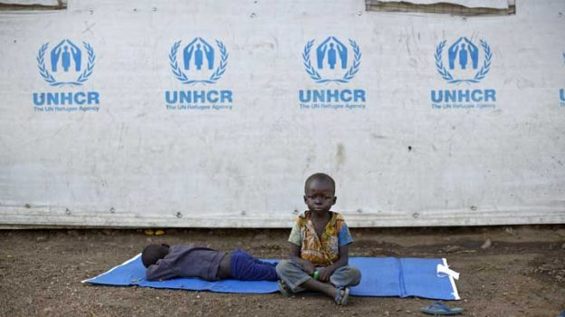 FILE - In this Friday, June 9, 2017 file photo, a South Sudanese refugee boy sits on a mat outside a communal tent while his brother sleeps, at the Imvepi reception center, where newly arrived refugees are processed before being allocated plots of land in nearby Bidi Bidi refugee settlement, in northern Uganda. The number of South Sudanese refugees sheltering in Uganda has reached 1 million, the United Nations said Thursday, Aug. 17, 2017, a grim milestone in what has become the world's fastest-growing refugee crisis. (AP Photo/Ben Curtis, File)