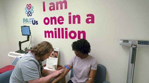 """In this Aug. 7, 2017, photo, Kenneth Parker Ulrich, left, a research technician at the University of Pittsburgh Medical Center, prepares to collect a blood sample from Erricka Hager, a participant in the """"All of Us"""" research program in Pittsburgh. The """"All of Us"""" research program is run by the National Institutes of Health and plans to track the health of at least 1 million volunteers by 2019. By doing so, researchers hope to learn how to better tailor treatments and preventative care to people's genes, environments, and lifestyle. The University of Pittsburgh is running a pilot program with some of the first enrollees in the study. (AP Photo/Dake Kang)"""