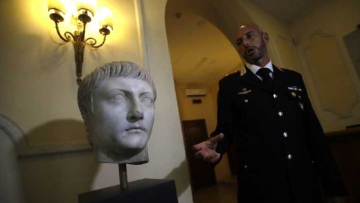 Italian Carabinieri officer Massimo Maresca shows the first century A.C. Druso marble head during an interview in the Carabinieri barracks, Friday, Sept. 1, 2017. The Cleveland Museum of Art gave it back to Italy after learning the piece depicting Emperor Tiberius' son had been stolen, apparently by Algerian troops, from southern Italy toward the end of World War II, brought into France, eventually sold at auction in Paris and acquired by the museum in 2012. (AP Photo/Alessandra Tarantino)
