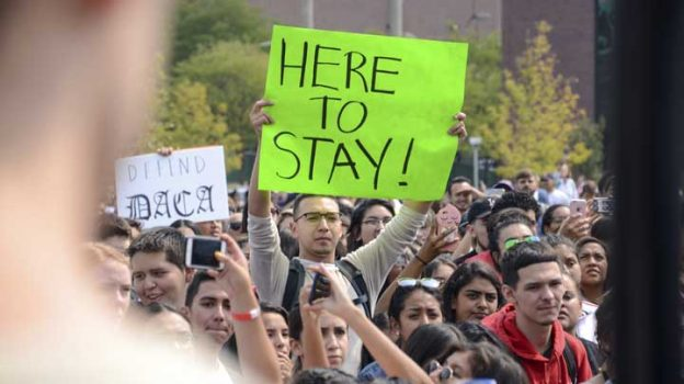 "FILE - In this Sept. 5, 2017 file photo, a protester holds a sign at a rally at Metropolitan State University after President Donald Trump's decision to repeal a program protecting young immigrants from deportation in Denver. Colleges and universities nationwide are stepping up efforts to help the students who are often called ""Dreamers,"" after the Trump administration announced plans last week to end that federal program protecting immigrants brought to the U.S. illegally as children. (AP Photo/Tatiana Flowers, File)"