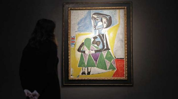 "A Christie's auction house staff member poses for photographs in front of the 1954 Pablo Picasso painting ""Femme accroupie (Jacqueline)"", a portrait of Jaqueline Roque, Picasso's final great muse and eventually his second wife, at their premises in London, Wednesday, Sept. 13, 2017. The painting is estimated to fetch between $20 and $30 million (16.7 and 25 million euro) in an Evening Sale of Impressionist and Modern Art on November 13 in New York. (AP Photo/Matt Dunham)"