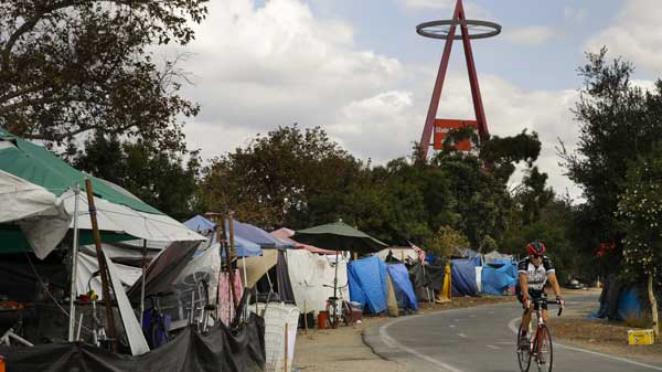 A cyclist passes the row of tents and tarps along the Santa Ana riverbed near Angel Stadium Thursday, Sept. 14, 2017, in Anaheim, Calif. Amid an uproar from residents, the city of Anaheim declared an emergency Wednesday in an attempt to cope with a ballooning homeless encampment along a popular riverbed trail and speed the addition of shelter beds. (AP Photo/Jae C. Hong)