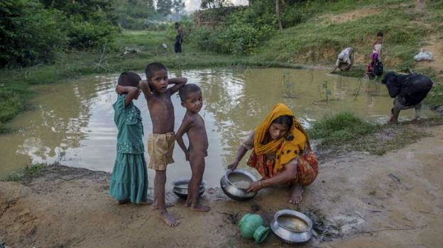A Rohingya Muslim woman cleans utensils near a polluted pond as her children stand near her in Kutupalong refugee camp, Bangladesh, Friday, Sept. 15, 2017. With Rohingya refugees still flooding across the border from Myanmar, those packed into camps and makeshift settlements in Bangladesh were becoming desperate for scant basic resources as hunger and illness soared. (AP Photo/Dar Yasin)