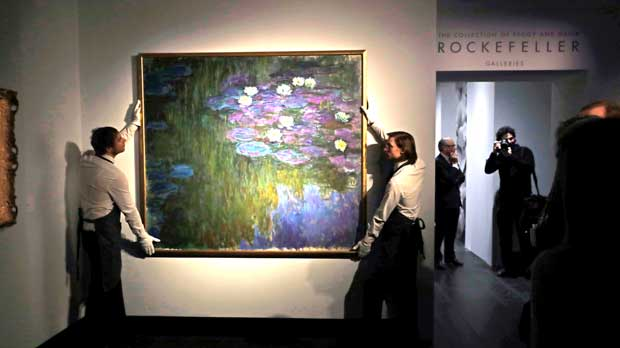 Christie's London auction house staff pose for photographs with Claude Monet's 'Nympheas en fleur', which will feature in the upcoming May 7-11 New York sale of the collection of Peggy and David Rockefeller, at their premises in London, Tuesday, Feb. 20, 2018. The painting is estimated to fetch $50 million-$70 million (35.7 million to 50 million pounds, 40.5million to 56.7 million euro). The art collection amassed by billionaire David Rockefeller could raise more than $500 million for charity when it is auctioned this spring. (AP Photo/Matt Dunham)