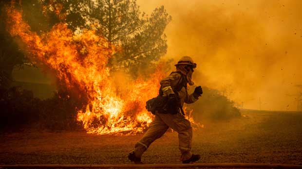 FILE - In this Tuesday, July 31, 2018, file photo, a firefighter runs while trying to save a home as a wildfire tears through Lakeport, Calif. The residence eventually burned. Authorities say a rapidly expanding Northern California wildfire burning over an area the size of Los Angeles has become the state's largest blaze in recorded history. It's the second year in a row that California has recorded the state's largest wildfire. (AP Photo/Noah Berger, File)