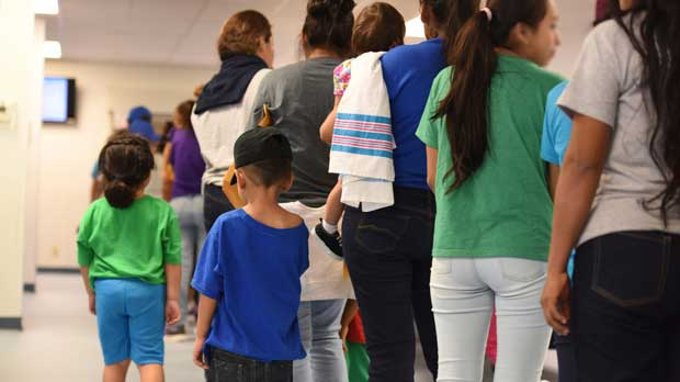 """In this Thursday, Aug. 9, 2018, photo, provided by U.S. Immigration and Customs Enforcement, mothers and their children stand in line at South Texas Family Residential Center in Dilley, Texas. Currently housing 1,520 mothers and their children, about 10 percent are families who were temporarily separated and then reunited under a """"zero tolerance policy"""" that has since been reversed. (Charles Reed/U.S. Immigration and Customs Enforcement via AP)"""