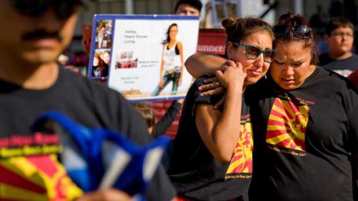 """Jenna Loring, left, the aunt of Ashley HeavyRunner Loring, cries with her cousin, Lissa Loring, during a traditional blanket dance before the crowd at the North American Indian Days celebration on the Blackfeet Indian Reservation in Browning, Mont., Saturday, July 14, 2018. The 'dance' was held to raise awareness and funds for Ashley's search. With just about 1,000 residents on the reservation, many folks are related and secrets have a way of spilling out. """"There's always somebody talking,"""" says Lissa, """"and it seems like to us since she disappeared, everybody got quiet. I don't know if they're scared, but so are we. That's why we need people to speak up."""" (AP Photo/David Goldman)"""