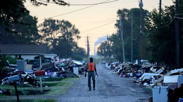 FILE - In this Sept. 28, 2017, file photo, a man walks past debris from homes on his street damaged in flooding from Hurricane Harvey as an oil refinery stands in the background in Port Arthur, Texas. Although many Texas families are still struggling to recover from Hurricane Harvey a year after it caused widespread damage and flooding along the Gulf Coast and in and around Houston, daily life has mostly returned to normal in many of the hardest hit communities. (AP Photo/David Goldman, File)