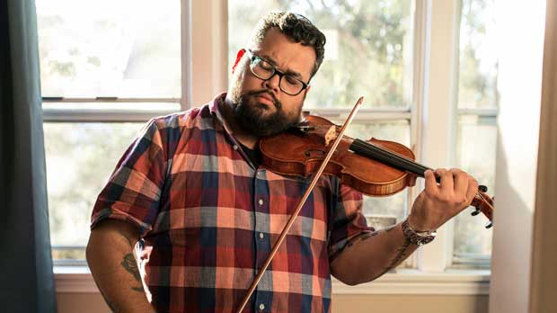 This Sept. 18, 2018 photo Provided by the John D. and Catherine T. MacArthur Foundation shows Robert Vijay Gupta, the Mark Houston Dalzell and James Dao-Dalzell First Chair Violin with the Los Angeles Philharmonic and Founder and Artistic Director of Street Symphony plays his violin in his house in Los Angeles. The John D. and Catherine T. MacArthur Foundation on Thursday Oct. 4, 2018 named Gupta and 24 other academics, activists, artists, scholars and scientists, MacArthur fellows. The recipients will receive $625,000 over five years to use as they please. (Photo by John D. and Catherine T. MacArthur Foundation via AP)