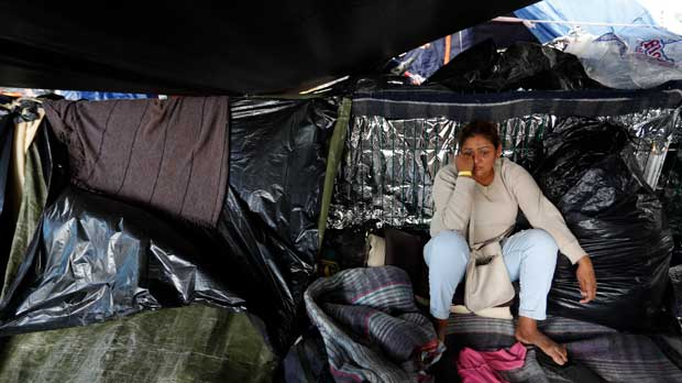 A woman from El Salvador waits to see whether the majority of migrants decide to move, as Central Americans debate individually whether to accept the city's plan to move them to a new shelter from the Benito Juarez sports complex, in Tijuana, Mexico, Friday, Nov. 30, 2018. Authorities in the Mexican city of Tijuana have begun moving some of more than 6,000 Central American migrants from an overcrowded shelter on the border to an events hall further away.(AP Photo/Rebecca Blackwell)