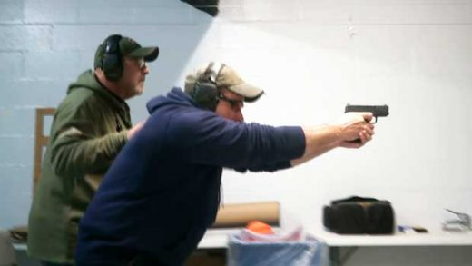 In this photo taken from a video shot on Nov. 28, 2018, Mike Carnevale places his hand on the back of Mark Hennesey while instructing him at the American Tactical Systems' indoor range in Green Island, New York. The application process for handgun licenses would be expanded under a bill before the New York state Legislature. The bill would require handgun applicants to turn over log-in information so investigators could look at three years' worth of Facebook, Snapchat, Twitter and Instagram postings. Google, Yahoo and Bing searches over the previous year also would be checked. (AP Photo/Michael Hill)
