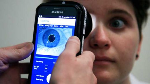 Clinical Research Assistant Kevin Jackson uses AlgometRx Platform Technology on Sarah Taylor's eyes to measure her degree of pain at the Children's National Medical Center in Washington, Monday, Dec. 10, 2018. Children's National Medical Center is testing an experimental device that aims to measure pain according to how pupils react to certain stimuli. (AP Photo/Manuel Balce Ceneta)