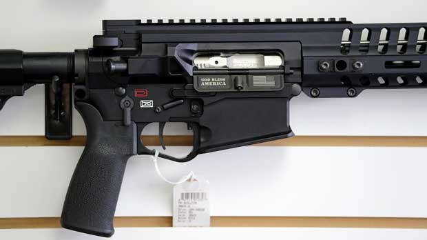 """FILE- In this Oct. 2, 2018, file photo, a semi-automatic rifle, with """"God Bless America"""" imprinted on it, is displayed for sale on the wall of a gun shop in Lynnwood, Wash. Starting Tuesday, Jan. 1, 2019, no one under the age of 21 in Washington state will be allowed to purchase a """"semi-automatic assault rifle,"""" under a voter-approved initiative that passed in November. (AP Photo/Elaine Thompson, File)"""