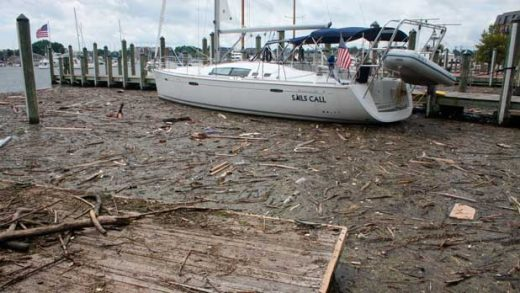 FILE - In this Aug. 1, 2018, file photo, debris washed into the Chesapeake Bay from record rainfall accumulates around a sailboat in Annapolis, Md. An annual report on the Chesapeake Bay says pollution from unusually heavy rains in 2018 contributed to the first decline in a decade in the overall health of the nation's largest estuary. (AP Photo/Brian Witte, File)