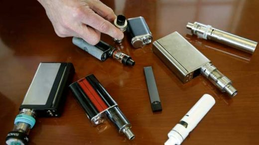FILE - In this April 10, 2018, file photo, a high school principal displays vaping devices that were confiscated from students in such places as restrooms or hallways at the school in Massachusetts. U.S. health officials are scrambling to keep e-cigarettes away from teenagers amid an epidemic of underage use. But doctors face a new dilemma: there are few effective options for weening young people off nicotine vaping devices like Juul. (AP Photo/Steven Senne, File)