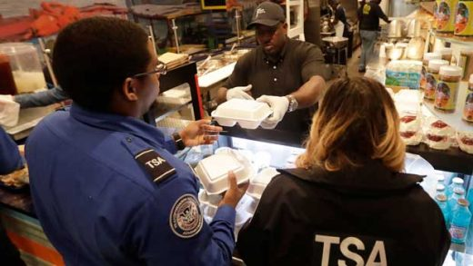 Chef Creole owner Wilkinson Sejour hands out free hot meals to TSA workers at his restaurant at Miami International Airport, Tuesday, Jan. 15, 2019, in Miami. The restaurant is offering free lunch and dinner to federal airport employees affected by the government shutdown. (AP Photo/Lynne Sladky)