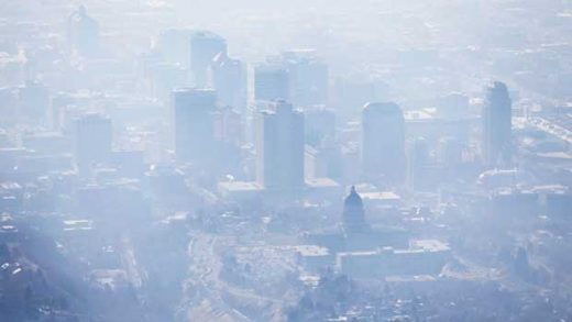 FILE - In this Jan. 18, 2017, file photo, smog covers Salt Lake City as an inversion lingers. When it comes to their views on climate change, Americans are looking at natural disasters and their local weather, according to a new poll. (Ravell Call/The Deseret News via AP, File)
