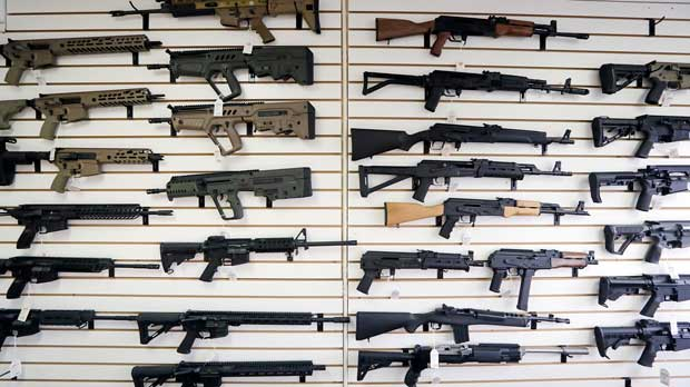 FILE - In this photo taken Oct. 2, 2018, semi-automatic rifles fill a wall at a gun shop in Lynnwood, Wash. A dozen county sheriffs in Washington state are refusing to enforce restrictions on semi-automatic rifles that voters approved in November. They say the new law might be unconstitutional, and they're waiting for the courts to weigh in. (AP Photo/Elaine Thompson, File)