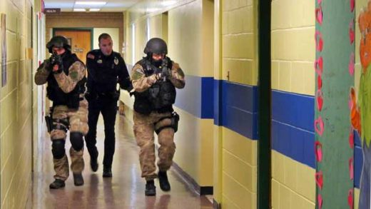 FILE - In this Jan. 28, 2013, file photo, members of the Washington County Sheriff's Office and the Hudson Falls Police Department use unloaded guns to take part in an emergency drill as they walk through a corridor inside the Hudson Falls Primary School in Hudson Falls, N.Y. With each subsequent shooting forcing schools to review their readiness, parents are increasingly questioning elements of the ever-evolving drills that are now part of most emergency plans, including the use of simulated gunfire and blood, when to reveal it's just practice, and whether drills unduly traumatize kids. (Omar Ricardo Aquije/The Post-Star via AP, File)
