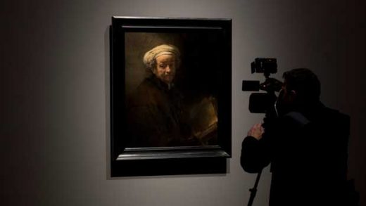 A guest takes pictures during a press preview of an exhibition of the all the Rijksmuseum's Rembrandts in Amsterdam, Netherlands, Wednesday, Feb. 13, 2019. To mark the 350th anniversary of the Dutch master's death, museums across the Netherlands have declared 2019 Rembrandt and the Golden Age Year and are staging a string of exhibitions to highlight their collections. (AP Photo/Peter Dejong)