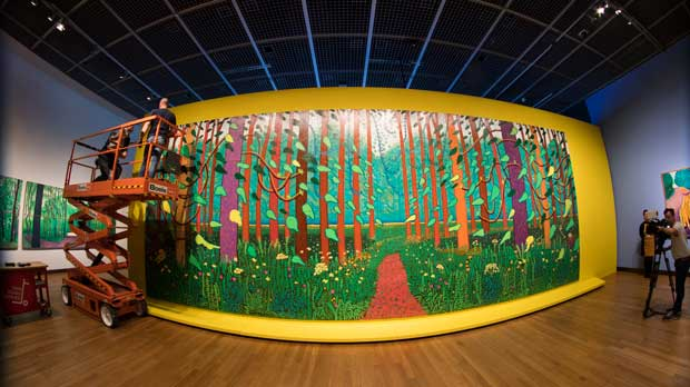 """Employees of the Van Gogh Museum make last adjustments when mounting the 32-canvas painting by David Hockney titled """"The Arrival of Spring in Woldgate"""" (East Yorkshire, 2011) prior to an exhibit in Amsterdam, Netherlands, Friday, Feb. 22, 2019. The exhibit """"Hockney-Van Gogh : The Joy of Nature"""" runs from March 1st till May 26th, 2019. (AP Photo/Peter Dejong)"""