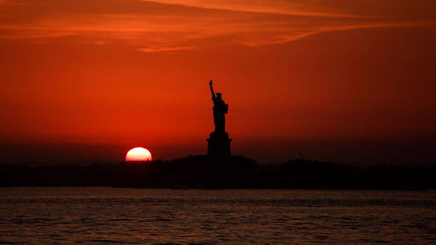 FILE - In this July 1, 2018 file photo, the sun sets behind the Statue of Liberty in New York as record high temperatures were recorded over the week in the U.S. and elsewhere. An AP data analysis of records from 1999-2019 shows that in weather stations across America, hot records are being set twice as often as cold ones. (AP Photo/Andres Kudacki, File)