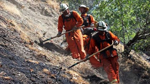 FILE - In this Jan. 17, 20014 file photo, firefighters clear brush as they battle the Colby Fire near Azusa, Calif. California is calling in the National Guard for the first time to help protect communities from wildfires like the one that destroyed much of the city of Paradise last fall. The state is pulling the troops away from President Donald Trump's border protection efforts in April 2019 and devoting them to fire protection, another area where the president has been critical of California officials. (AP Photo/Jae C. Hong, File)