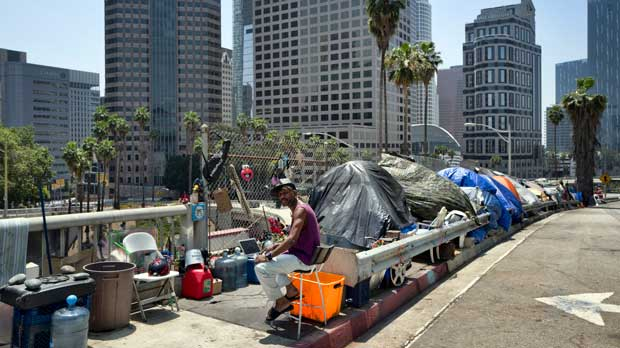 FILE - In this May 10, 2018 file photo, a homeless man sits at his tent along the Interstate 110 freeway in downtown Los Angeles. California Gov. Gavin Newsom met with the mayors of some of California's largest cities to discuss the homeless situation Wednesday March 20,2019. Newsom and the mayors are asking the legislature for more money on top of the $500 million the state has already given cities for programs assisting the homeless. (AP Photo/Richard Vogel, File)