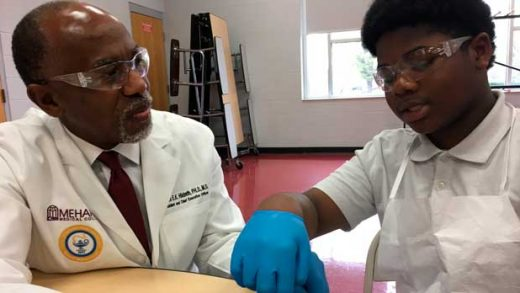 Dr. James Hildreth dissects a frog Friday, March 29, 2019, with seventh grader Keyshawn Walker at the Haynes Middle Health/Medical Science Design Center in Nashville, Tenn. Hildreth is president and CEO of Nashville's Meharry Medical College, the nation's oldest historically black medical school. He and about 200 Meharry faculty and medical students were at Haynes to help inspire the students to pursue medical careers, in part by providing them real life examples of people who look like them who have achieved success in medicine. (AP Photo/Travis Loller)