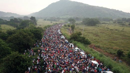 FILE - In this Oct. 27, 2018 file photo, members of a US-bound migrant caravan stand on a road after federal police briefly blocked their way outside the town of Arriaga, Mexico. Activists, officials and social workers in Central America were staggered by the idea that U.S. President Donald Trump thinks he will help reduce immigration by cutting off nearly $500 million in aid to Honduras, Guatemala and El Salvador; exactly the opposite will happen, they say. (AP Photo/Charlie Riedel, File)