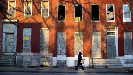 FILE-In this March 30, 2013 file photo, a woman walks past blighted row houses in Baltimore. New annual estimates from the U.S. Census Bureau show that Baltimore is continuing to shed inhabitants. Census data released Thursday, April 18, 2019 shows that Maryland's biggest city lost an estimated 7,346 citizens during the 12 months that ended July 1. (AP Photo/Patrick Semansky, File)