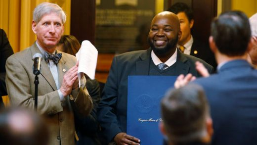 FILE - In this Jan. 24, 2019 file photo Virginia Teacher of the Year, Rodney Robinson, center right, smiles as he is honored on the floor of the Virginia House of Delegates as Del. Steven Landes, R-Augusta, left, applauds during the House session at the Capitol. Robinson was named Wednesday, April 24 as the 2019 National Teacher of the Year. He will spend the next year traveling around the country as an ambassador for education and an advocate for teachers and students. (AP Photo/Steve Helber)