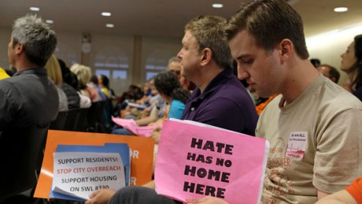 Two men hold signs while listening to public comment about a proposed homeless shelter during a meeting of the Port Commission Tuesday, April 23, 2019, in San Francisco. San Francisco port commissioners are deciding whether to approve a new homeless shelter along the city's touristy and residential Embarcadero. (AP Photo/Eric Risberg)