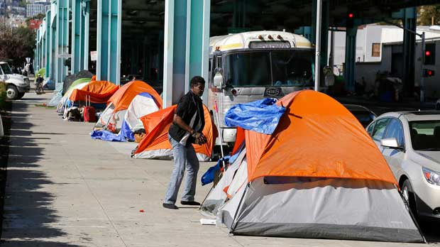 FILE - In this Feb. 23, 2016, file photo, a man stands outside his tent on Division Street in San Francisco. A key federal count shows the number of homeless people increased by double-digit percentages in three San Francisco area counties over two years. In San Francisco, the number of homeless people jumped 17% to more than 8,000 in 2019. (AP Photo/Eric Risberg, File)