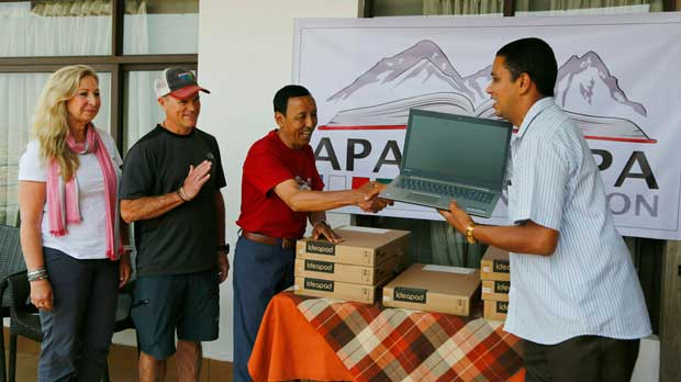 In this May 9, 2019, photo, Apa Sherpa, center, hands over a computer to Chakra Karki, representative of a school from Dhuske, Okhaldhunga district in Kathmandu, Nepal. Apa Sherpa has stood on top of the world more times than all but one other person. Now he wants to make sure no one feels compelled to follow in his footsteps. (AP Photo/Niranjan Shrestha)