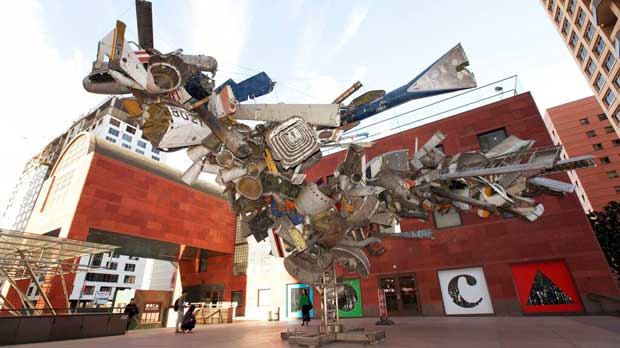 """FILE - This Jan. 6, 2014, file photo shows """"Airplane Parts,"""" a sculpture by Nancy Rubins made of scraps of old airplanes wired together into a massive junk tree, greeting visitors to the Museum of Contemporary Art, MOCA, in downtown Los Angeles. The Museum of Contemporary Art in downtown Los Angeles says admission will soon be free thanks to a $10 million gift by the president of its board of trustees. Carolyn Powers announced her donation during an annual benefit dinner. (AP Photo/Nick Ut, File)"""