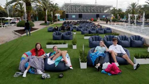 people sit outdoors to watch a movie as part of a program offered by the Miami Dolphins at Hard Rock Stadium