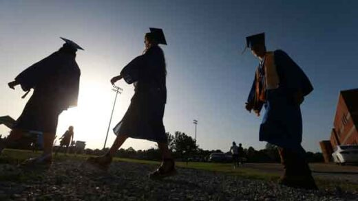 Saltillo High School seniors make their way to the football field as the sun begins to set for their graduation ceremony