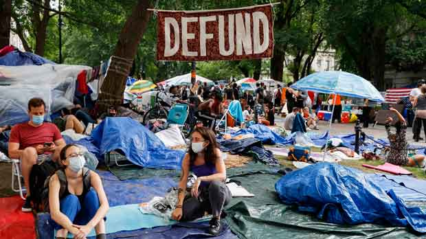 "Protesters gather under a sign reading ""DEFUND"" at an encampment outside City Hall"