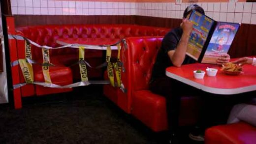 A dine-in customer looks at a menu next to a dining booth taped off for social distancing