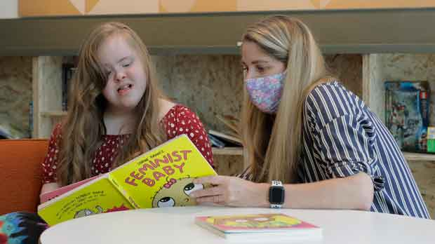 Tricia Nora, right, a pediatric nurse practitioner, reads a book to Emilyanne Wade
