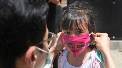 Olivia Chan's father helps her with a new mask she received during a graduation ceremony for her Pre-K class
