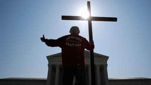 Tom Alexander holds a cross as he prays prior to rulings outside the Supreme Court on Capitol Hill